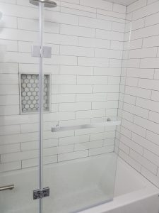Updated bathroom shower with new white subway tiles, fixtures and glass door.