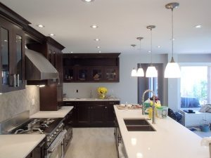 Renovated kitchen with dark wood cupboards and white countertops. Kitchen island features updated sink and fixtures.